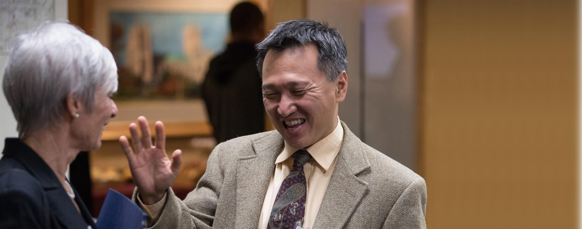 A picture of a man smiling and waving at the Internationalization Collaborative event