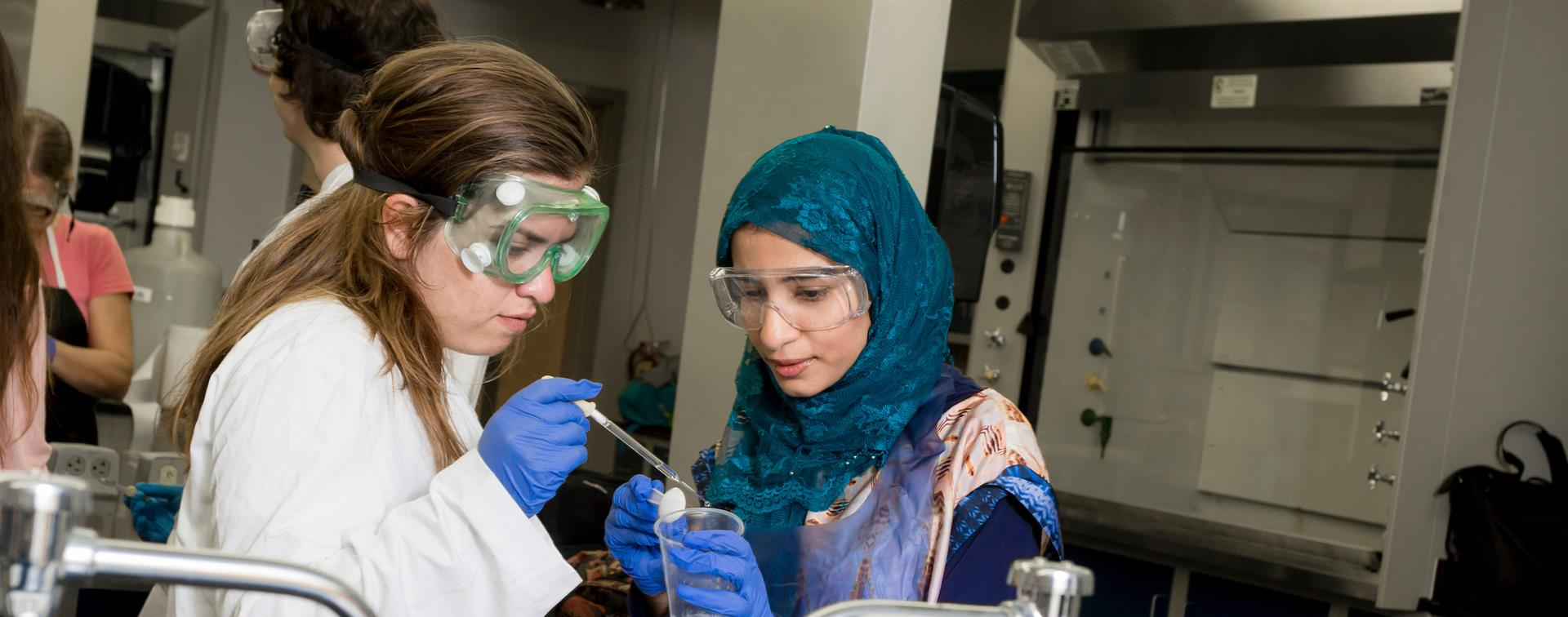A picture of two women in a lab running an experiment