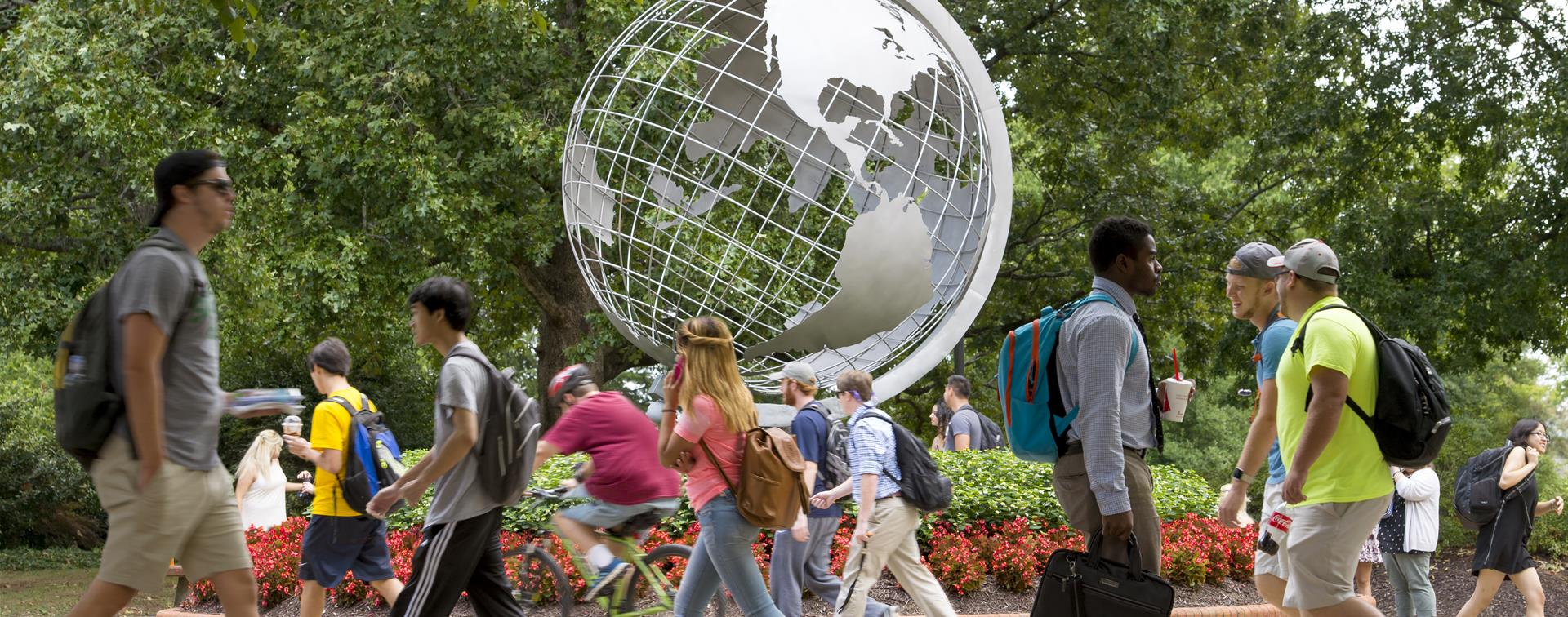 Picture of students walking on campus in front of a statue of a globe.