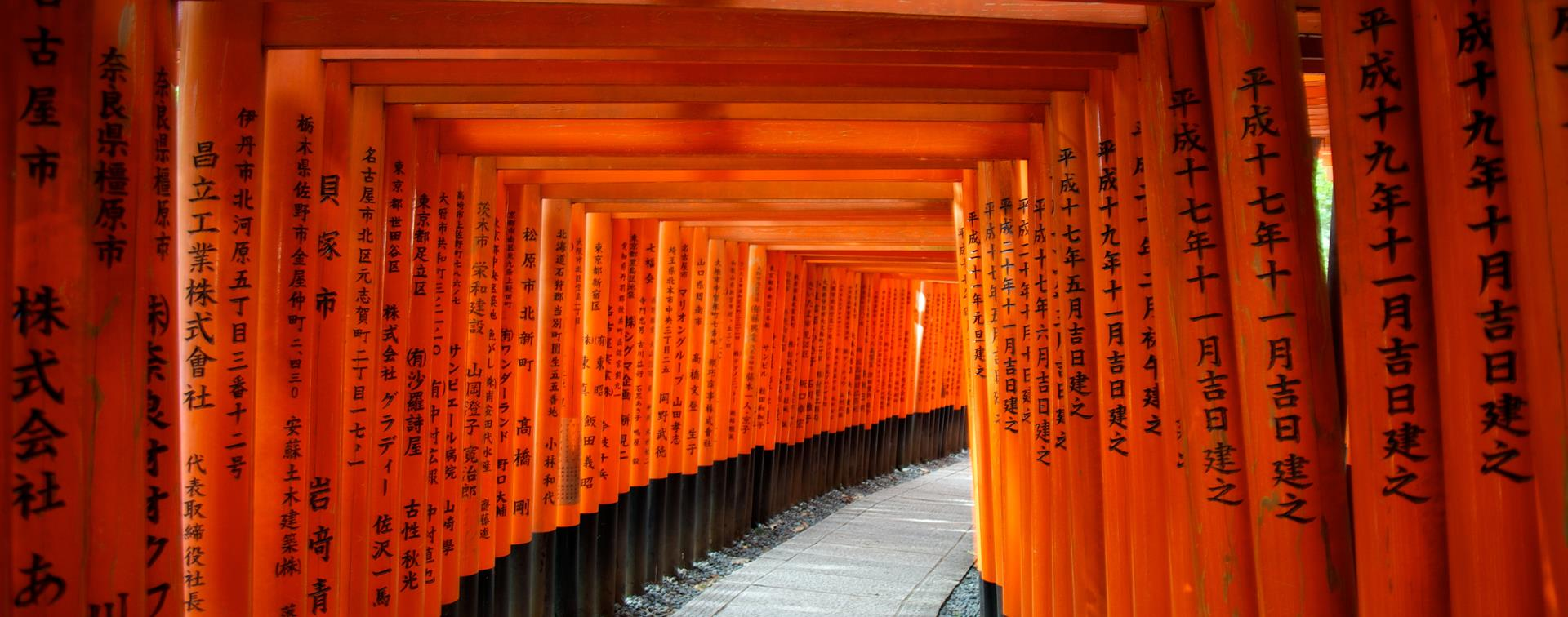 The orange Torii Gates in Japan, with black lettering on them.