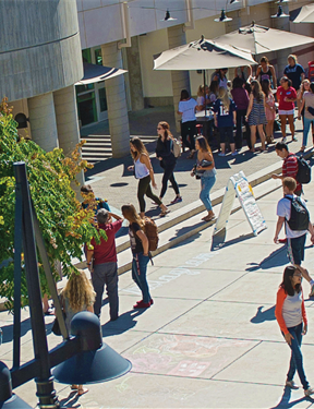 Picture of a campus center with students walking.