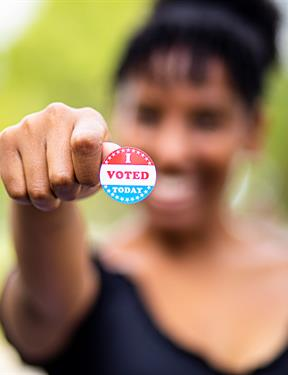 "Picture of young woman holding ""I Voted"" sticker"