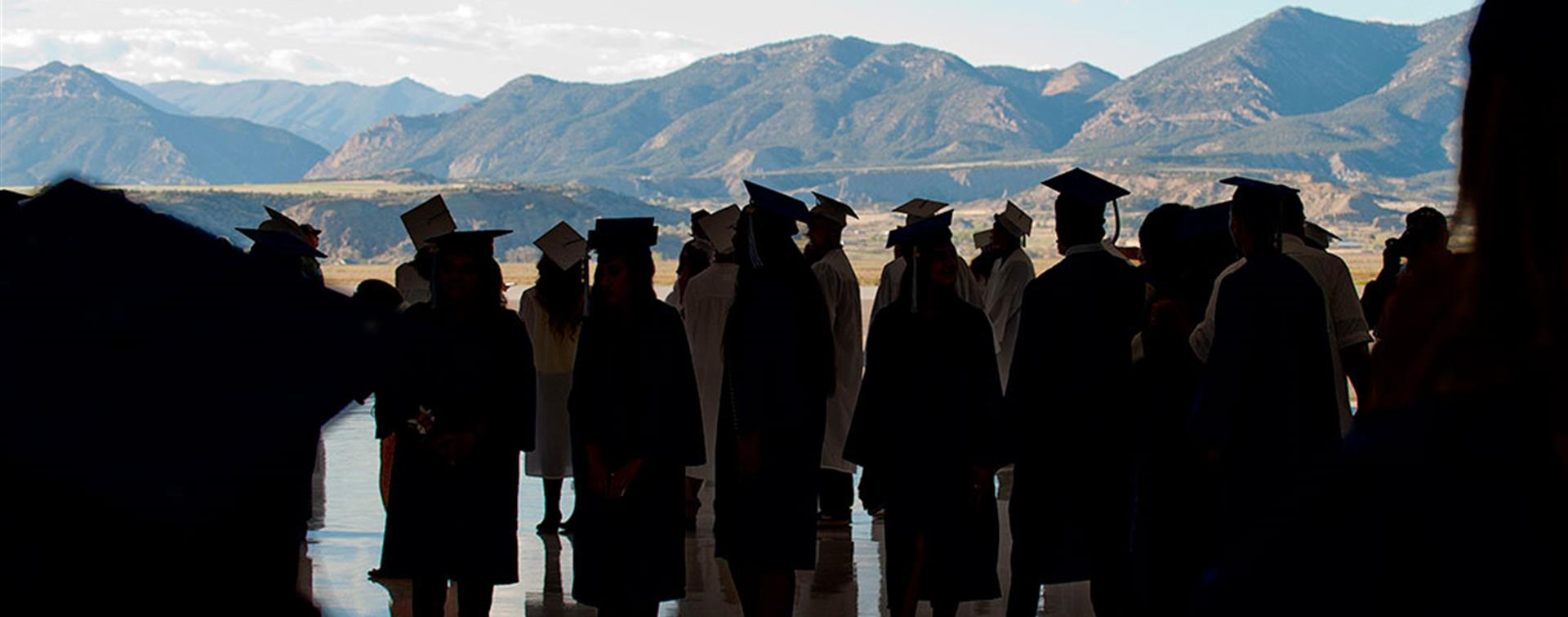 Colorado Mountain College graduates standing before a mountain backdrop