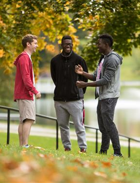 Picture of three students on campus having a conversation.