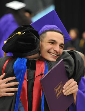 Picture of student hugging an adult at New Mexico Highlands University graduation ceremony